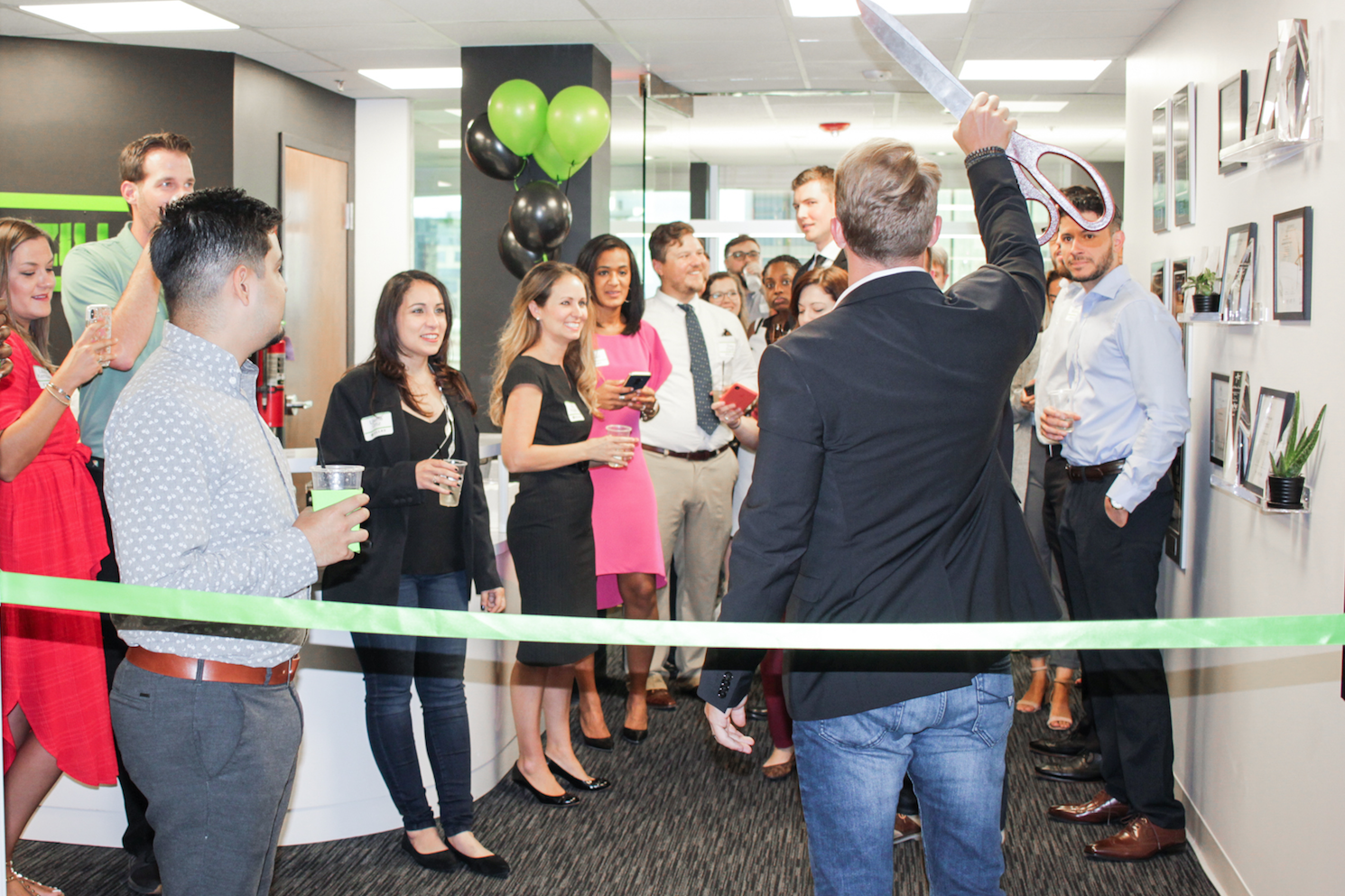 Designzillas' CEO Johnny Hughes Holds Up Giant Scissors for Ribbon-Cutting Ceremony