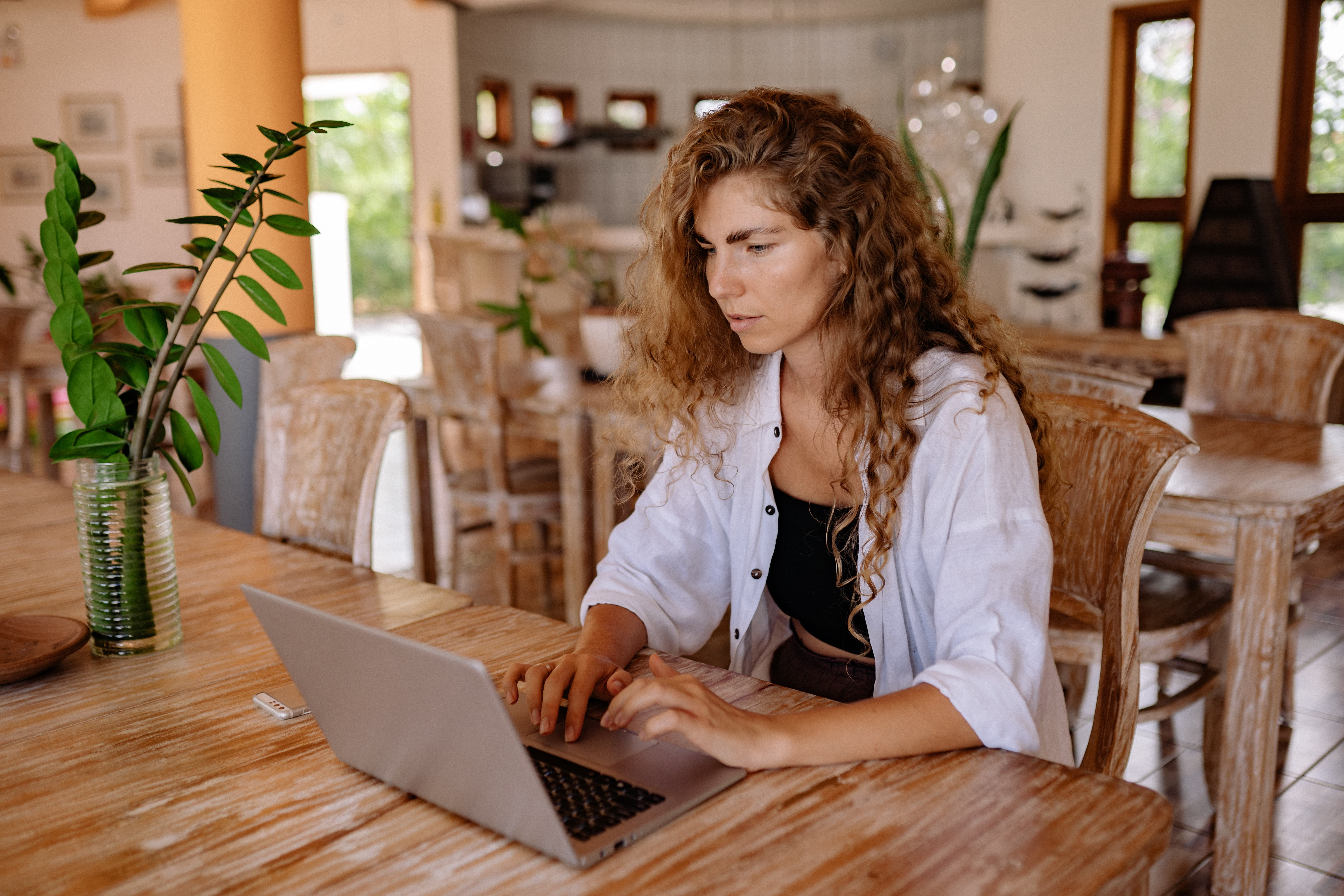 woman sitting at table using a laptop